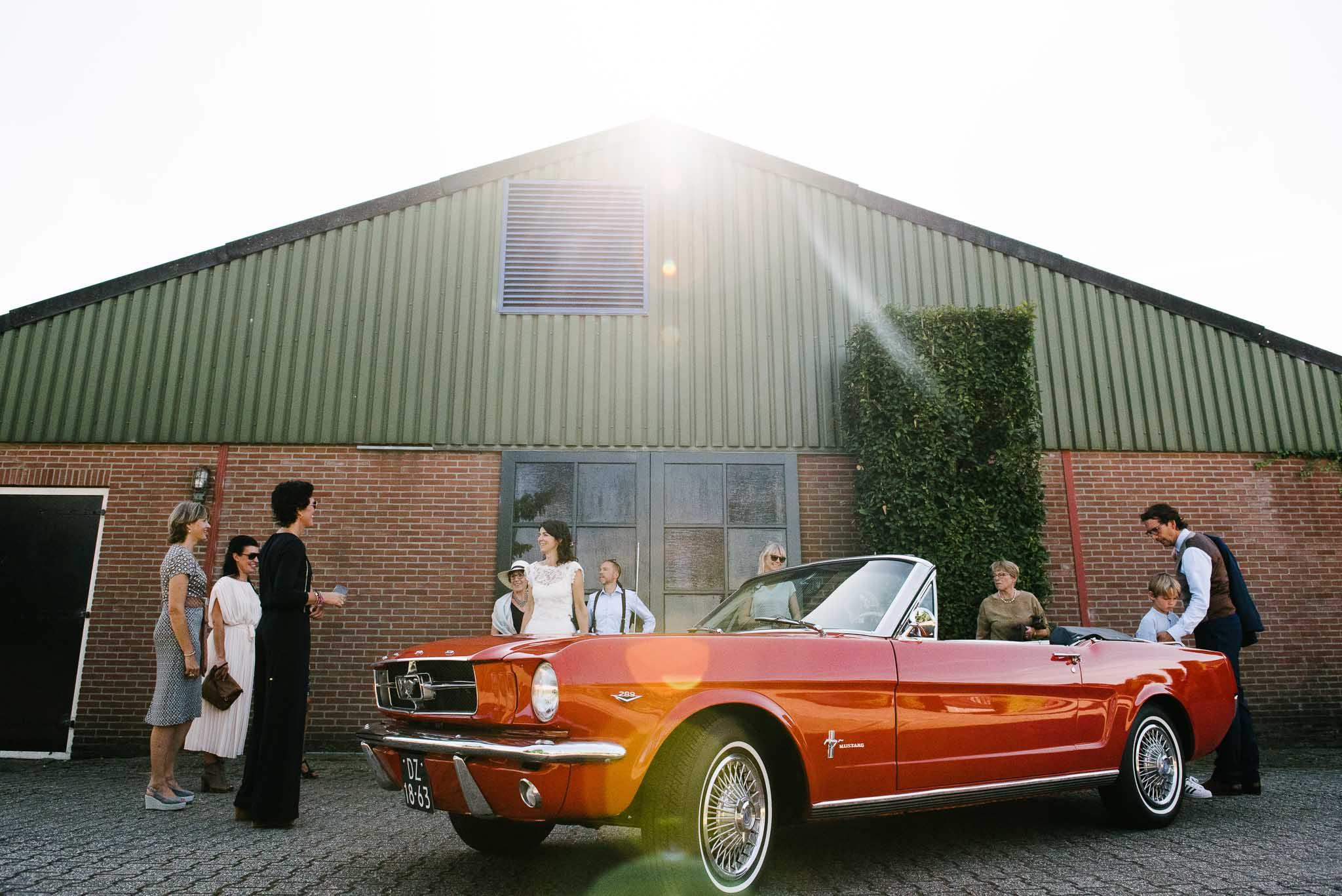 journalistieke bruidsfotografie Arnhem rode Ford Mustang trouwauto